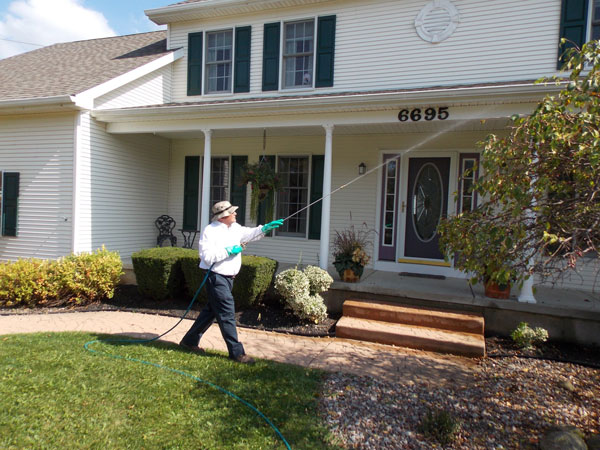 man walking in front yard of a house, spraying insecticide on gutters of the house